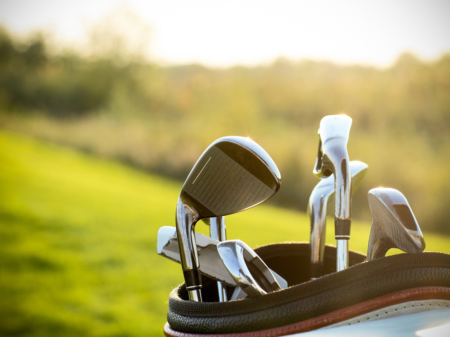 Golf clubs sit in a bag on the hill in the evening sunset. Someone is enjoying the golf course at Leduc Golf Club, or